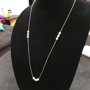 Long, formal faux gold and pearl necklace